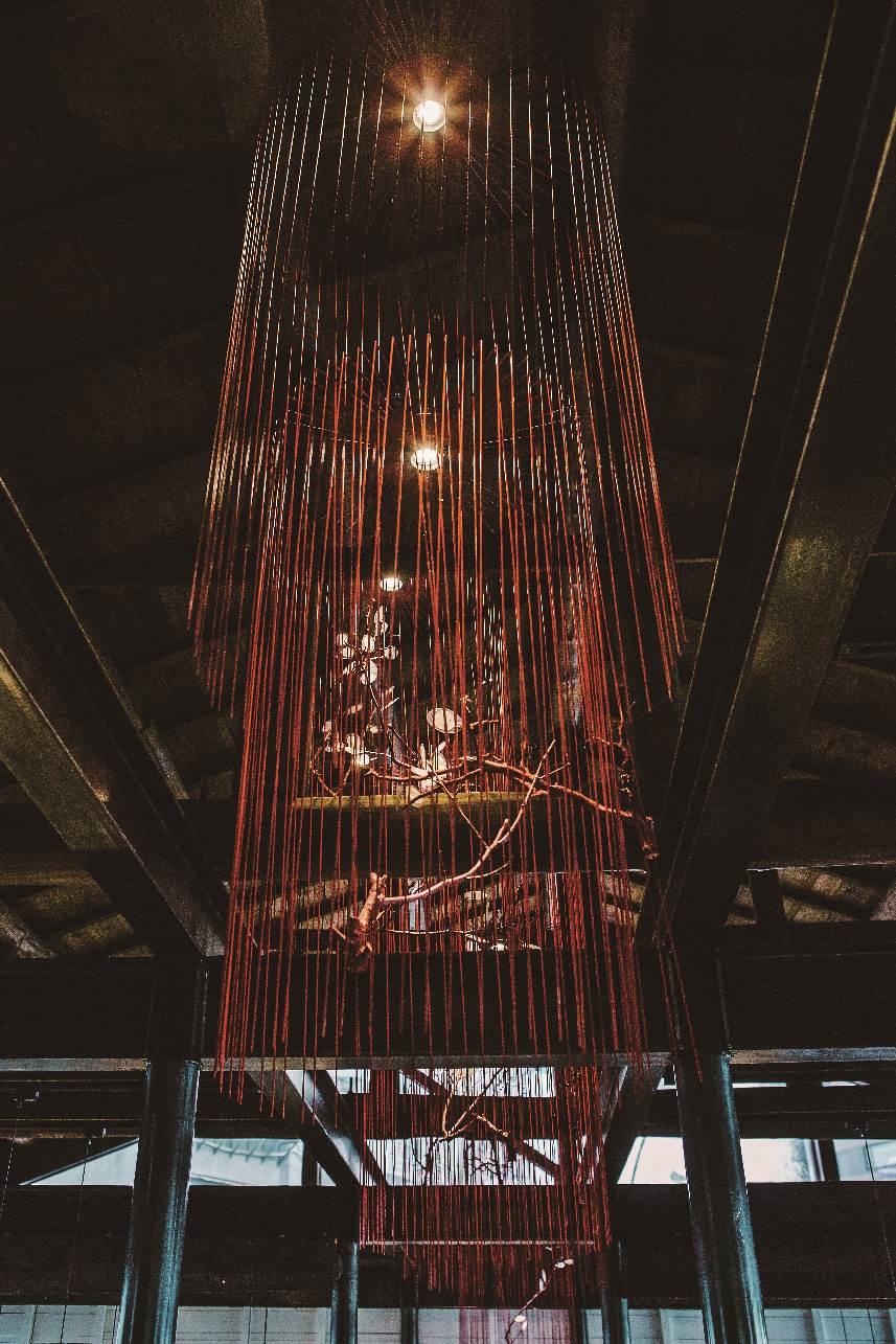 高處垂吊著紅色鳥籠,帶有東方象徵。